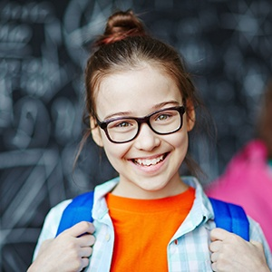 Young girl sporting spectacles and backpack smiling