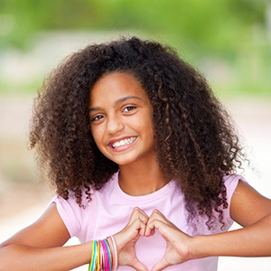 Young girl making heart sign and smiling