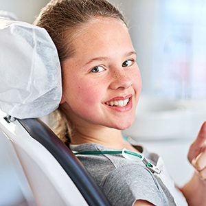 Young girl sitting on dental chair smiling
