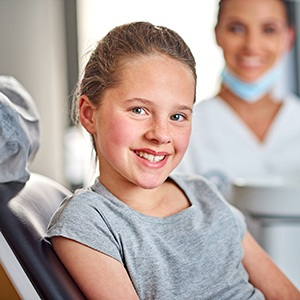 Young child resting on dental chair smiling