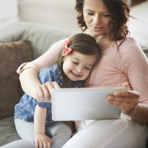 Mother and Daughter enjoying playing on tablet