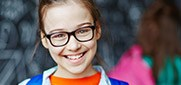 Young child with glasses smiling brightly