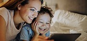 mother and child looking at tablet laughing