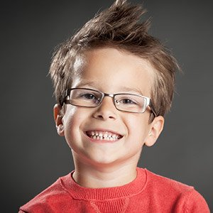 Young boy in red wearing glasses smiling