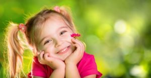 little girl hands on face smiling