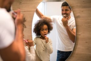 Father and daughter brushing their teeth in front of a mirror