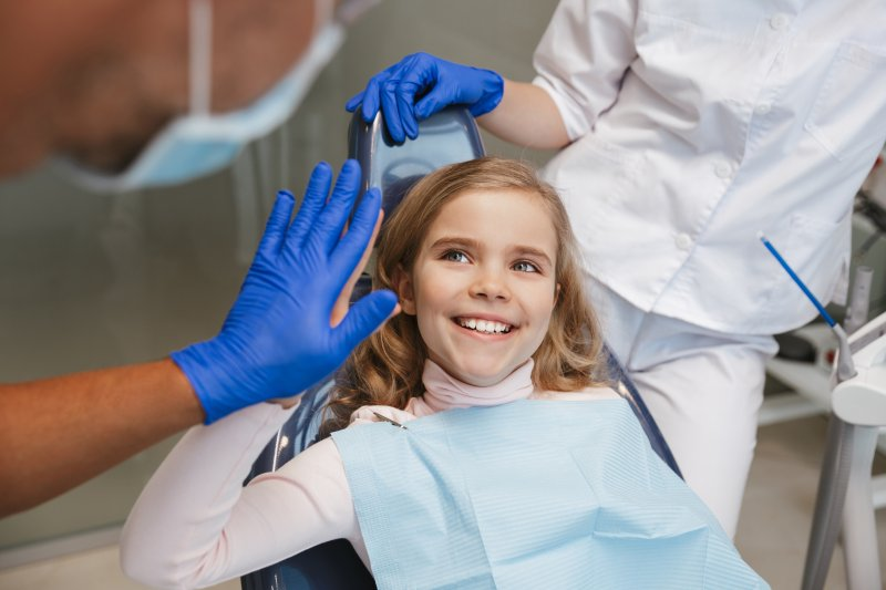 Young girl giving dentist high-five in treatment chair