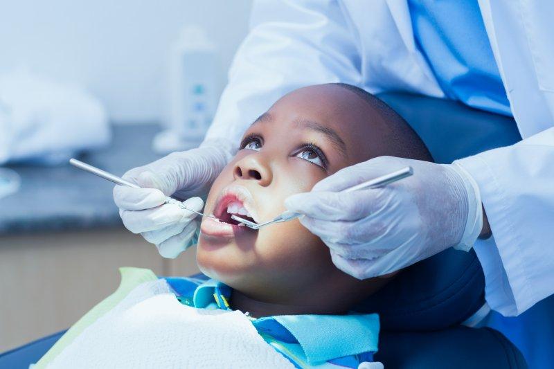 Dentist examining child's teeth and gums at dental checkup