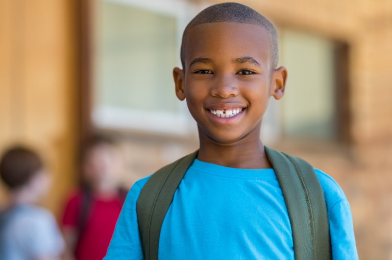 Child in blue shirt smiling at school